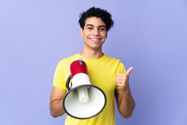 Young venezuelan man isolated on purple holding a megaphone with thumb up