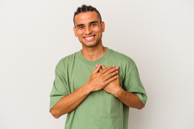 Young venezuelan man isolated on white background laughing keeping hands on heart, concept of happiness.