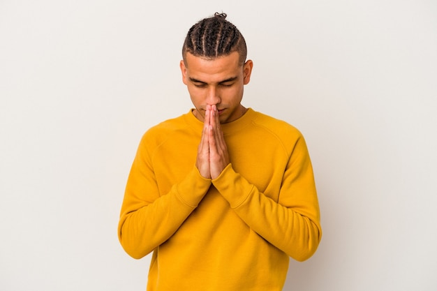 Young venezuelan man isolated on white background praying, showing devotion, religious person looking for divine inspiration.
