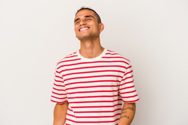 Young venezuelan man isolated on white background relaxed and happy laughing, neck stretched showing teeth.