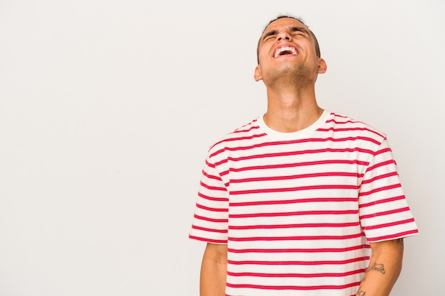 Young venezuelan man isolated on white background shouting very angry, rage concept, frustrated.