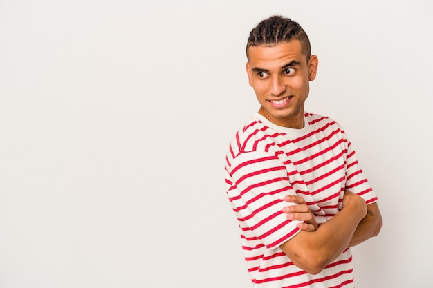 Young venezuelan man isolated on white background smiling confident with crossed arms.