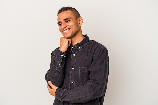 Young venezuelan man isolated on white background smiling happy and confident, touching chin with hand.