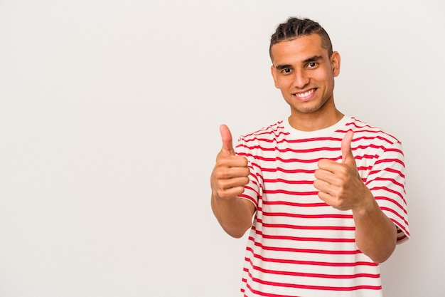 Young venezuelan man isolated on white background smiling and raising thumb up