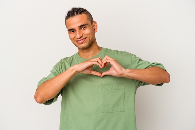 Young venezuelan man isolated on white background smiling and showing a heart shape with hands.