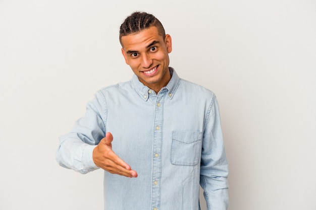Young venezuelan man isolated on white background stretching hand at camera in greeting gesture.