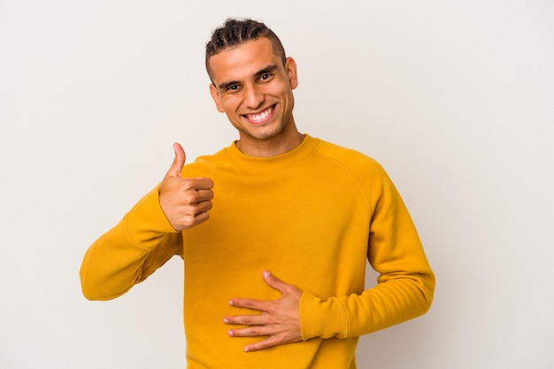 Young venezuelan man isolated on white background touches tummy, smiles gently, eating and satisfaction concept.