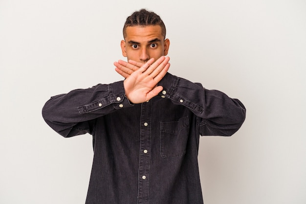Young venezuelan man isolated on white wall doing a denial gesture