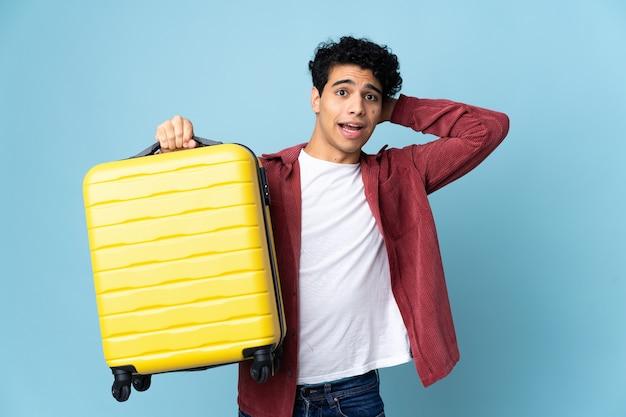 Молодой венесуэльский мужчина на синем в отпуске с чемоданом и удивлен