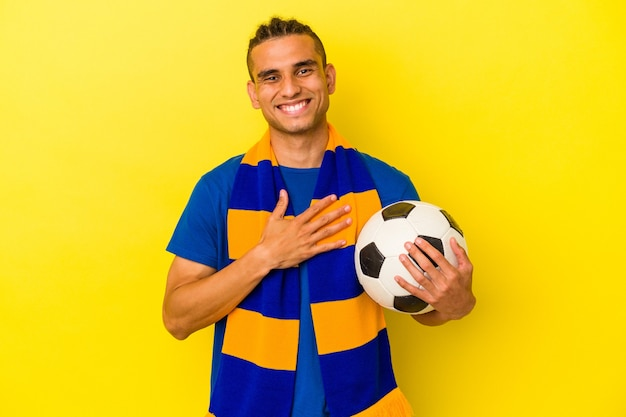 黄色の背景に分離されたサッカーを見ている若いベネズエラの男は、胸に手を置いて大声で笑います。