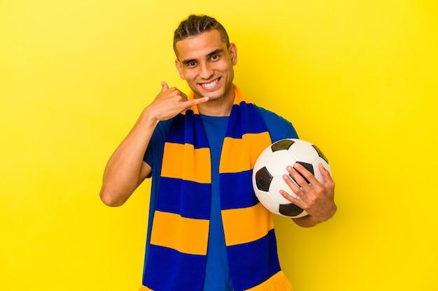 指で携帯電話の呼び出しジェスチャーを示す黄色の背景に分離されたサッカーを見ている若いベネズエラの男。
