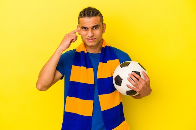 Young venezuelan man watching soccer isolated on yellow background showing a disappointment gesture with forefinger.