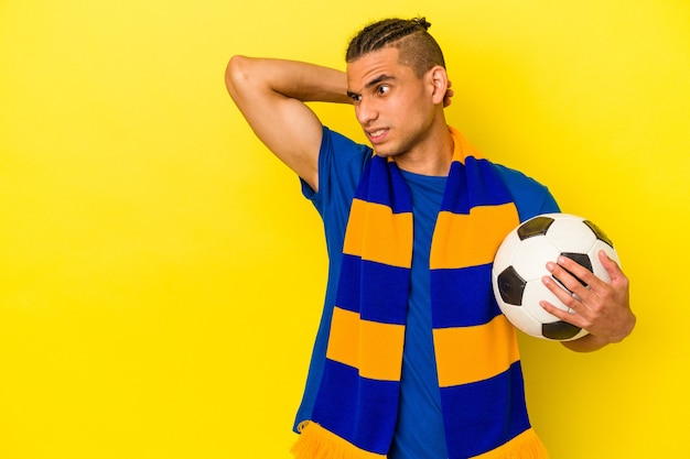Young venezuelan man watching soccer isolated on yellow background touching back of head, thinking and making a choice.