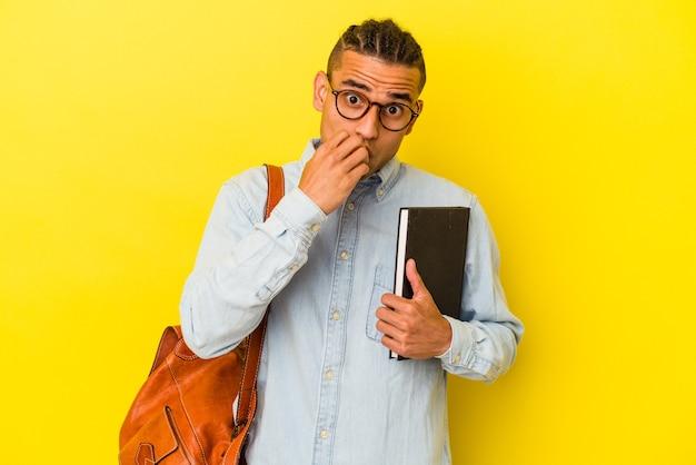 若いベネズエラの学生男性は、黄色の背景に爪を噛んで孤立し、神経質で非常に心配しています。