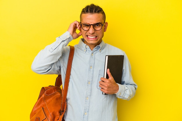 手で耳を覆う黄色の背景に分離された若いベネズエラの学生男性。