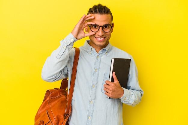 黄色の背景に孤立した若いベネズエラの学生の男は、目に大丈夫なジェスチャーを維持して興奮しました。