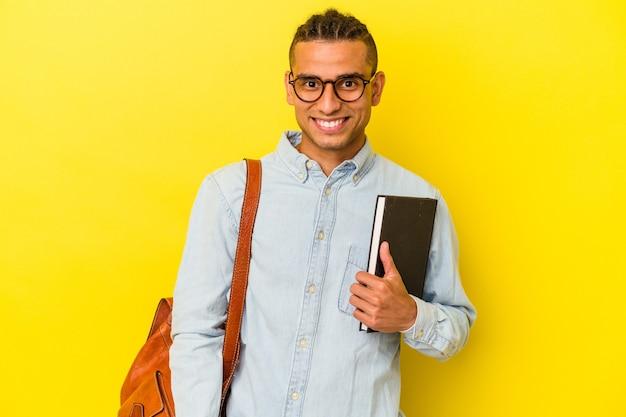 黄色の背景に孤立した若いベネズエラの学生の男は幸せ、笑顔、陽気な。