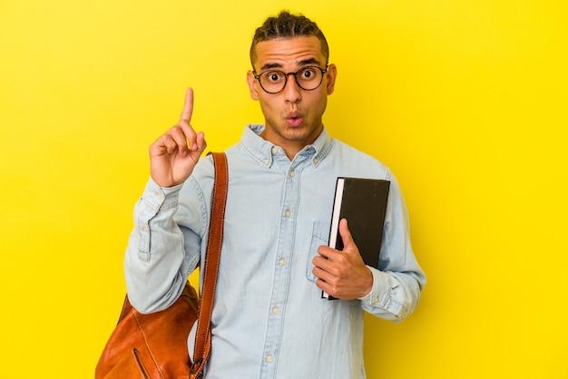 いくつかの素晴らしいアイデア、創造性の概念を持っている黄色の背景に分離された若いベネズエラの学生の男。