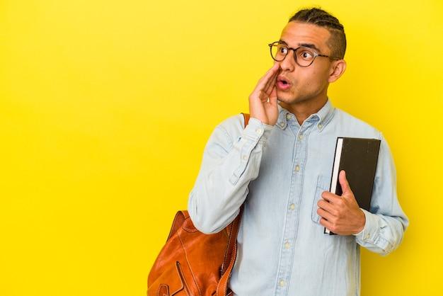 黄色の背景に孤立した若いベネズエラの学生男性は、秘密のホットブレーキのニュースを言って脇を見ています