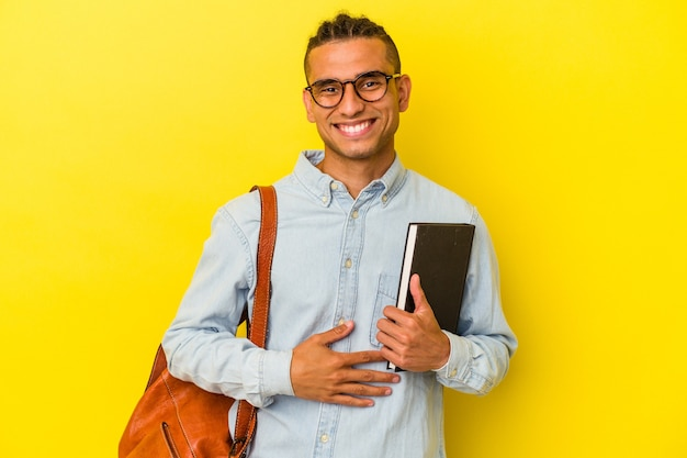 笑って楽しんで黄色の背景に孤立した若いベネズエラの学生の男。