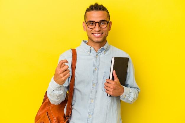 黄色の背景に孤立した若いベネズエラの学生男性が、招待状が近づくように指で指さします。