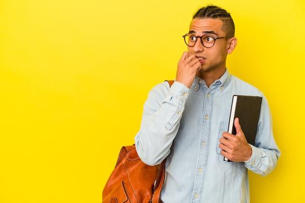 黄色の背景に孤立した若いベネズエラの学生男性は、コピースペースを見ている何かについて考えてリラックスしました。