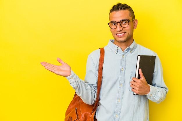 手のひらにコピースペースを示し、腰に別の手を保持している黄色の背景に分離された若いベネズエラの学生男性。