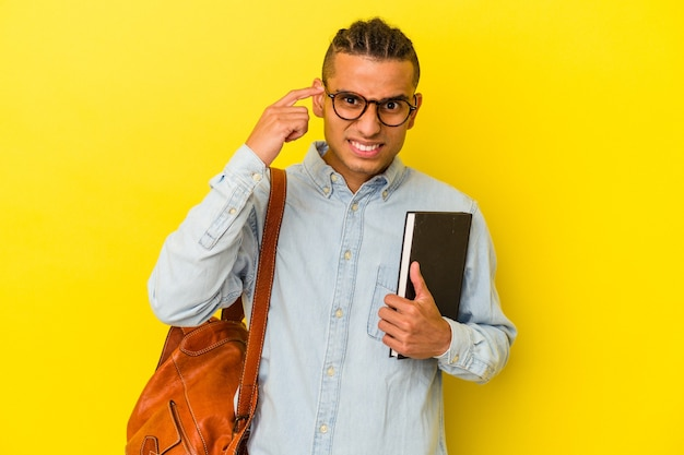人差し指で失望のジェスチャーを示す黄色の背景に分離された若いベネズエラの学生男性。