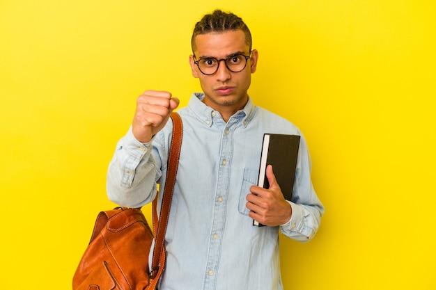 カメラに拳、攻撃的な表情を示す黄色の背景に分離された若いベネズエラの学生男性。
