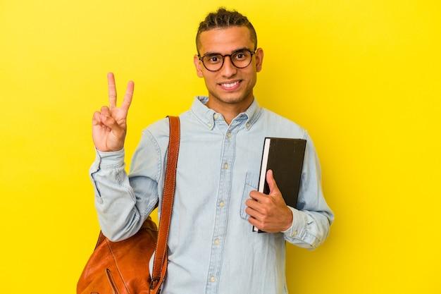 指で2番目を示す黄色の背景に分離された若いベネズエラの学生男性。