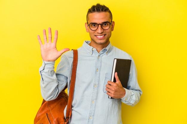 黄色の背景に孤立した若いベネズエラの学生の男は、指で5番を示して陽気に笑っています。