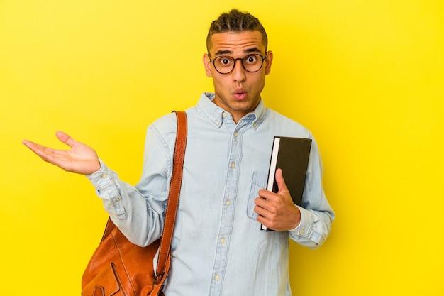 黄色の背景に孤立した若いベネズエラの学生男性は驚いてショックを受けました。
