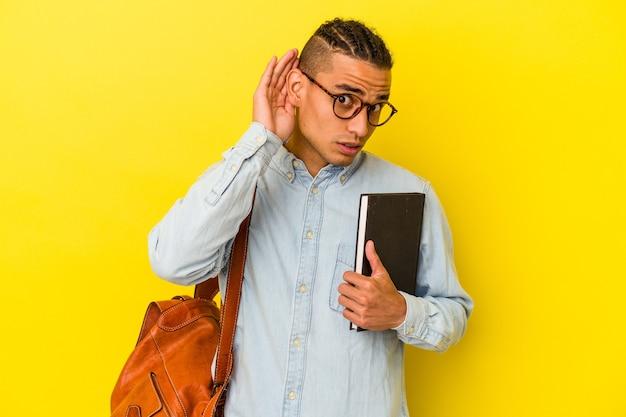 ゴシップを聞いてみて黄色の背景に孤立した若いベネズエラの学生男性。