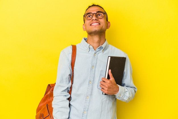 Young venezuelan student man isolated on yellow background dreaming of achieving goals and purposes