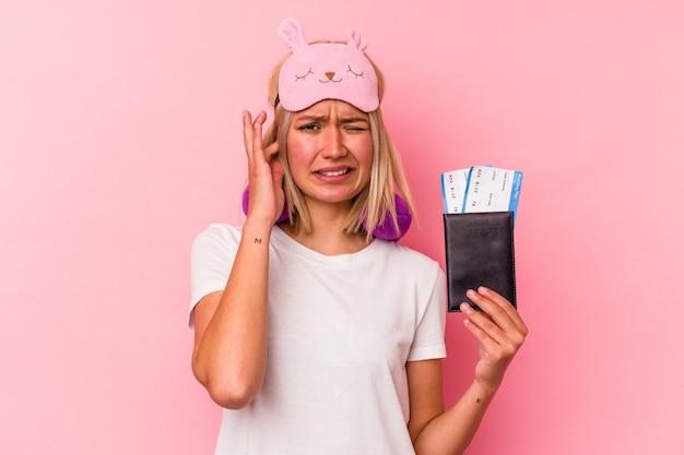 手で耳を覆うピンクの背景に分離されたパスポートを保持している若いベネズエラの旅行者の女性。