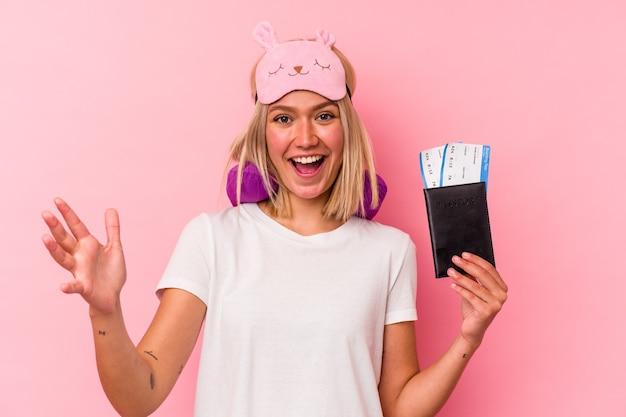 ピンクの背景で隔離のパスポートを保持している若いベネズエラの旅行者の女性は、嬉しい驚きを受け取り、興奮し、手を上げます。