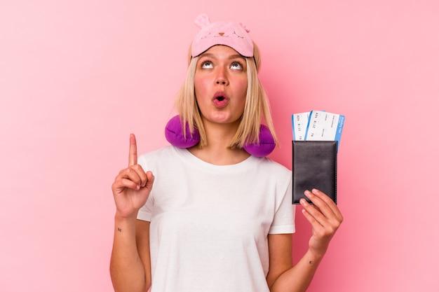 열린 된 입으로 거꾸로 가리키는 분홍색 벽에 고립 된 여권을 들고 젊은 베네수엘라 여행자 여자.