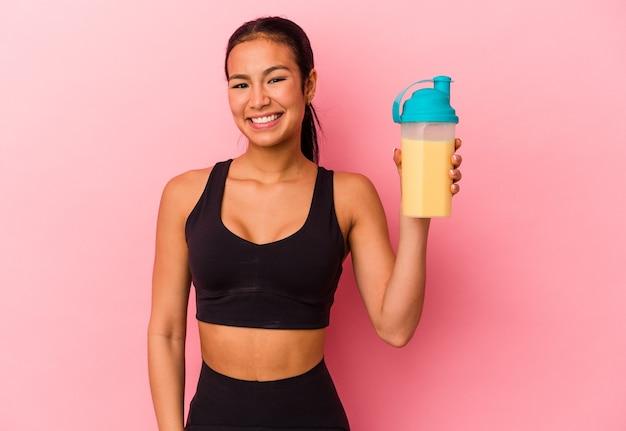 ピンクの背景に分離されたプロテインシェイクを飲む若いベネズエラの女性は幸せ、笑顔、陽気な。