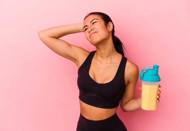 머리 뒤쪽을 만지는 분홍색 배경에 격리된 단백질 쉐이크를 마시는 젊은 베네수엘라 여성