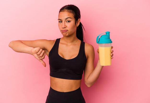 Молодая венесуэльская женщина пьет протеиновый коктейль на розовом фоне