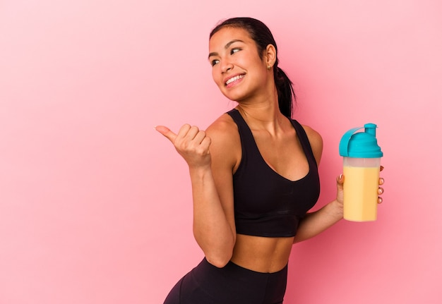 Young venezuelan woman drinking a protein shake isolated on pink background