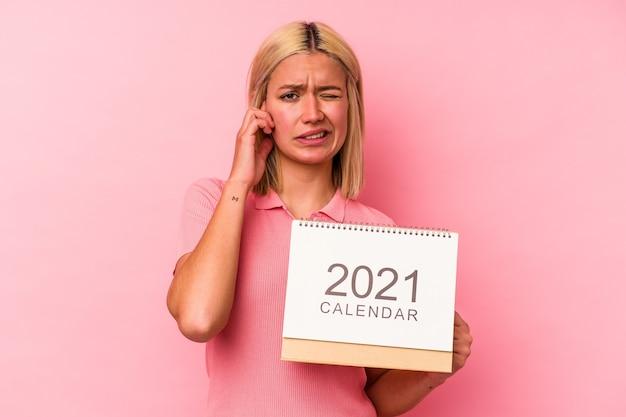 手で耳を覆うピンクの背景に分離されたカレンダーを保持している若いベネズエラの女性。