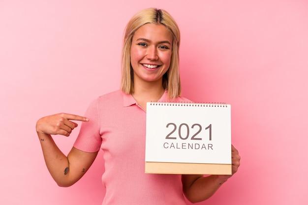 Молодая венесуэльская женщина, держащая календарь на розовом фоне, гордая и уверенная в себе, указывая рукой на пространство для копирования рубашки