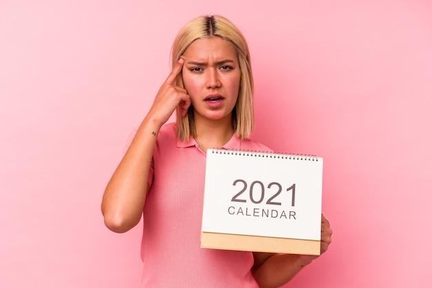 Молодая венесуэльская женщина, держащая календарь, изолированный на розовом фоне, показывает жест разочарования указательным пальцем.