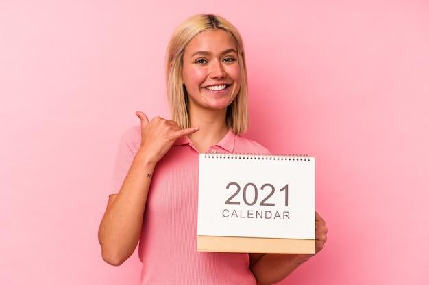 指で携帯電話の呼び出しジェスチャーを示すピンクの背景で隔離のカレンダーを保持している若いベネズエラの女性。
