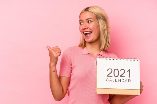 Молодая венесуэльская женщина, держащая календарь, изолированный на розовой стене, указывает пальцем в сторону, смеясь и беззаботно.