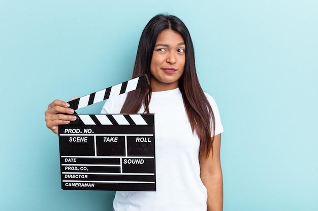 Молодая венесуэльская женщина, держащая с 'хлопушкой', изолированную на синем фоне, смущена, чувствует себя сомнительной и неуверенной.