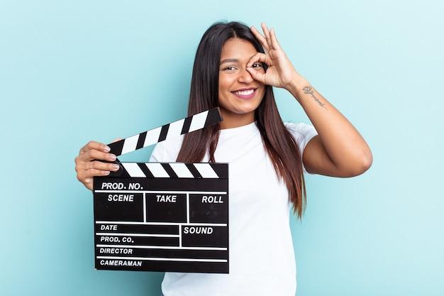 Молодая венесуэльская женщина, держащая с 'хлопушкой', изолированную на синем фоне, взволнована, держа на глазах одобренный жест.