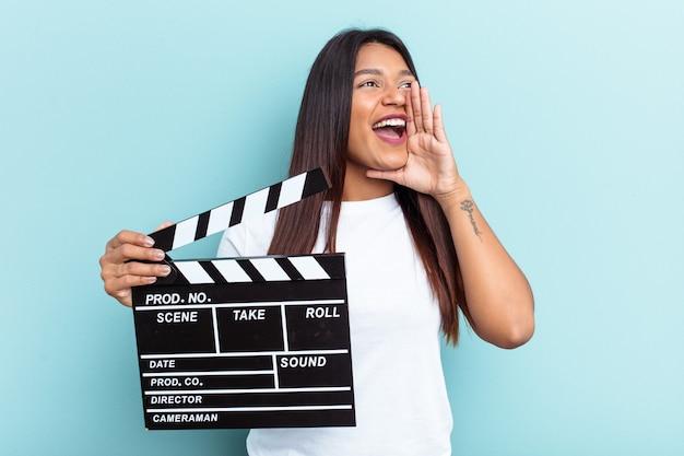 Молодая венесуэльская женщина, держащая с 'хлопушкой', изолированную на синем фоне, кричит и держит ладонь возле открытого рта.