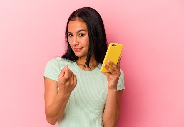 ピンクの背景で隔離された携帯電話を持っている若いベネズエラの女性は、招待が近づくようにあなたに指を指しています。